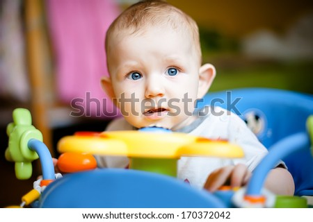Small beautiful baby in a walker. - stock photo