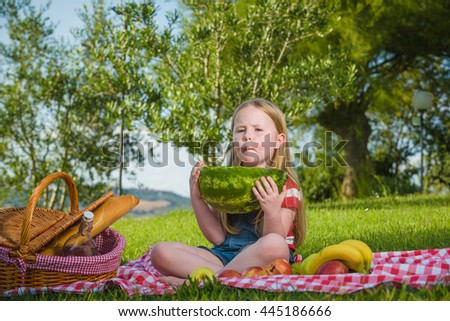 Small beautiful blond girl doing picnic in the landscape of Tuscan countryside.