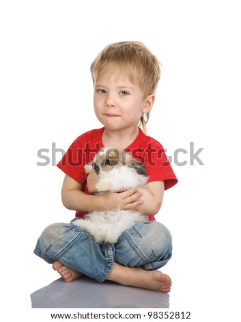 Small beautiful boy embraces an amusing rabbit. isolated on white background - stock photo