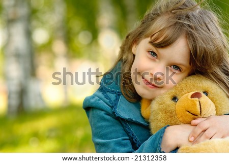 Small beautiful girl embraces an amusing bear cub against  summer nature. - stock photo