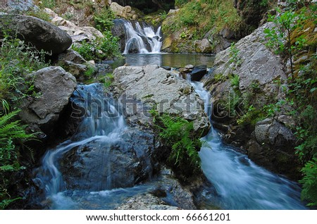 Small beautiful waterfall on a mountain river (with long exposure) - stock photo