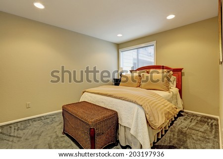 Small bedroom with dark green carpet floor, one bed and wicker ottoman