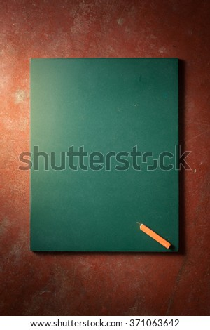 Small black board in green color with blank space for text or message on veteran red cement background with low key scene