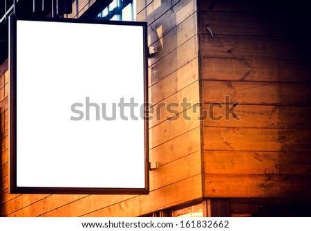 Small blank billboard on the wooden building - stock photo