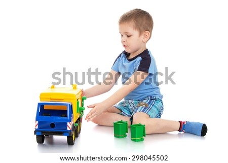 small blond boy in a blue t-shirt and shorts is sitting on the floor playing in kindergarten in a plastic truck-Isolated on white - stock photo
