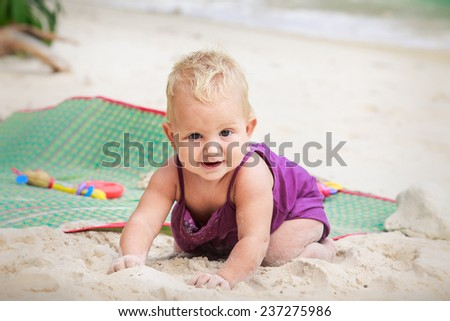 small blonde baby girl in violet dress crawling on the white sand on the beach