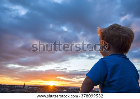 Small blonde boy expressing excitement over beautiful sunset sky. - stock photo