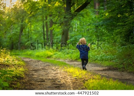 Small blonde boy playing in forest. Natural landscape with small caucasian boy.
