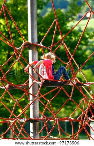 small blonde girl climbing a rope climbing frame wearing a pink T-shirt and blue jeans - stock photo