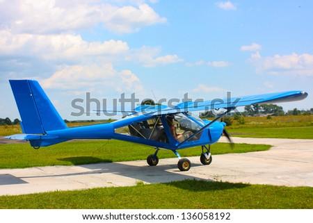 small blue airplane under sky in field taken in summer in Ukraine - stock photo