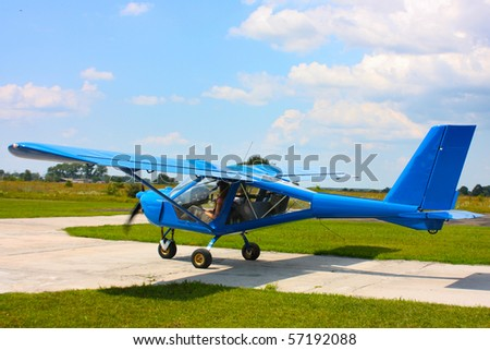 small blue airplane under sky in field taken in summer in Ukraine - stock photo