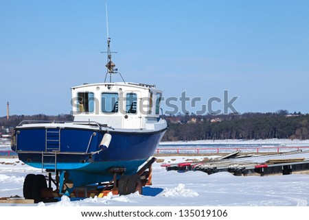 Small blue boat on the snowy coast of Baltic Sea in winter