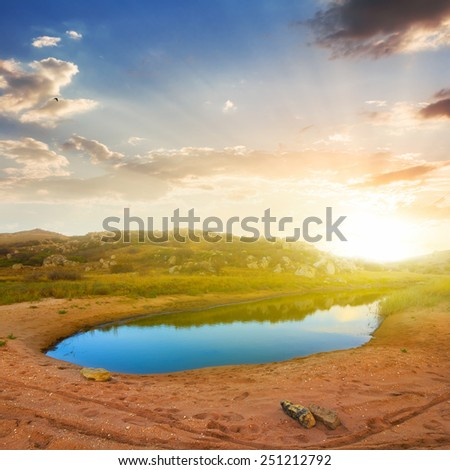 small blue lake in a sandy desert - stock photo