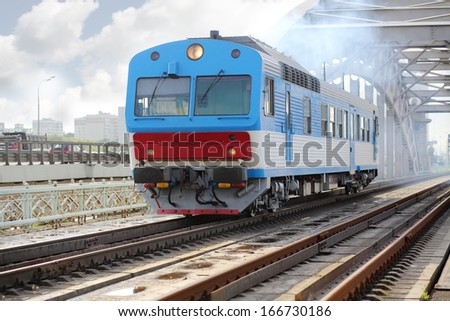 Small blue train rides rails on railway bridge at summer day. - stock photo