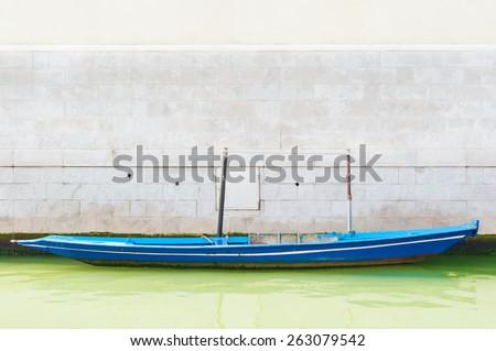 Small boat against brick wall in Venice, Italy. - stock photo