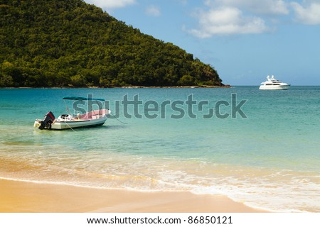 Small boat and yacht floating on the clear waters of the Caribbean - stock photo