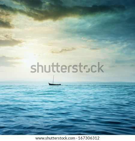 Small boat floats in the sea. - stock photo