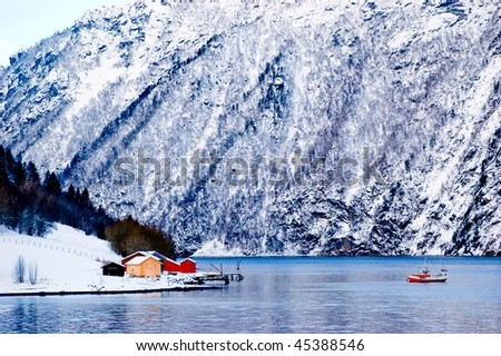 Small boat in the fjord in Norway, winter - stock photo