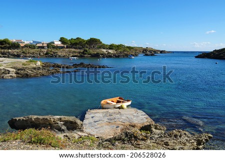 small boat on a cove in the Mediterranean sea, Cadaques, Catalonia, Costa Brava, Spain - stock photo