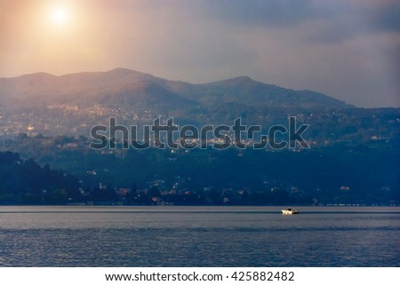 small boat on the background of the big mountain.Toning. The picture is noise.Italy, Arona. - stock photo