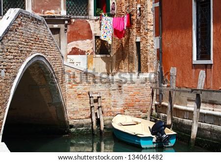 Small boat under bridge on small street in Venice, Italy. - stock photo