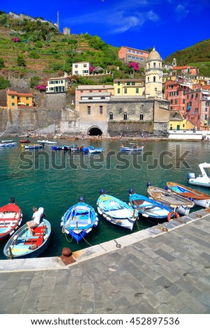 Small boats by the pier and Santa Margherita d'Antiochia church in Vernazza, Cinque Terre, Italy