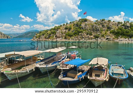 small boats moored in Aegean sea blue lagoon with mountainous islands around, beach at background and turkish flag at top of hill in Turunc, Mugla, Turkey - stock photo