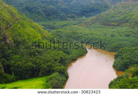 Small boats moving down a placid river through the jungle