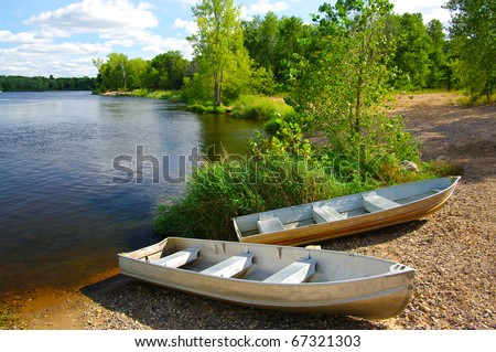 Small Boats on Shore: Small fishing boats wait on the shore of a Wisconsin lake. - stock photo