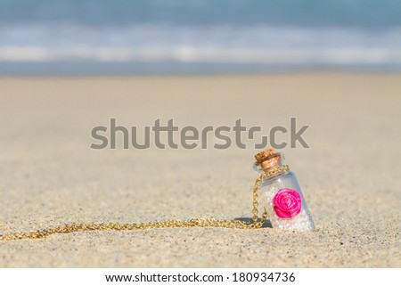 Small bottle in white sandy beach background the turquoise sea - stock photo