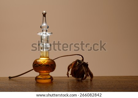 Small bottle of perfume on table decorated with dried flower