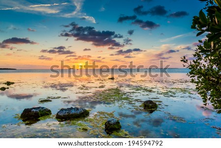 Small boulders frame sunset in Key Largo, FL - stock photo