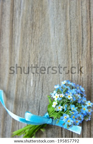 Small bouquet of blue forget-me-not, tied a blue ribbon, on the background of old wooden plank, selective focus - stock photo
