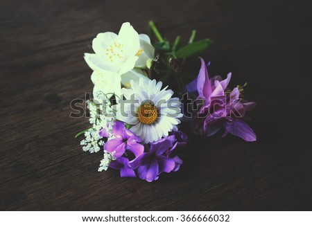 Small bouquet of white daisy, aquilegia and jasmine flowers on wooden table.