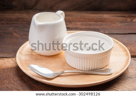 small bowl jar and teaspoon on wooden plate background - stock photo