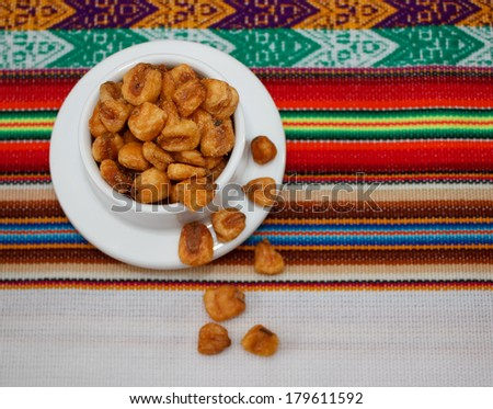 Small bowl of toasted salted corn seeds on peruvian tablecloth - stock photo