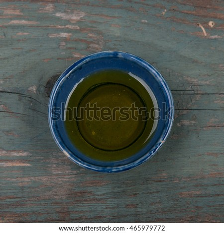 Small bowl of vinegar on a wooden table