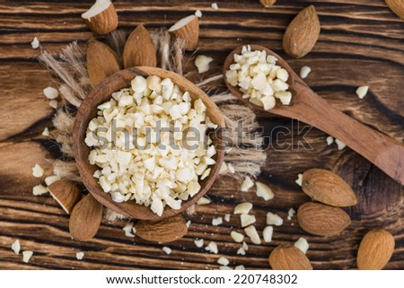 Small bowl with Minced Almonds (close-up shot) on rustic wooden background - stock photo
