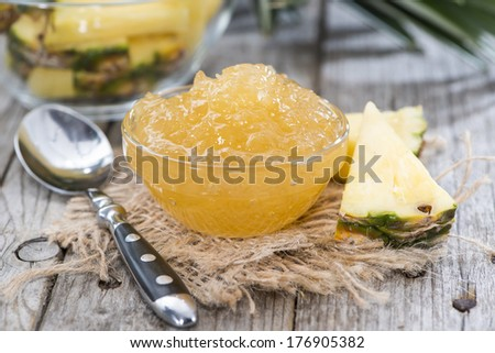 Small bowl with Pineapple Jam (close-up shot on wood) - stock photo