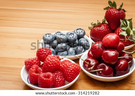 Small bowls of fruit containing cherries, strawberries, blueberries and rasberries on a wooden table