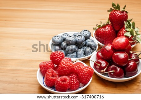 Small bowls of fruit containing cherries, strawberries, blueberries and rasberries on a wooden table - stock photo