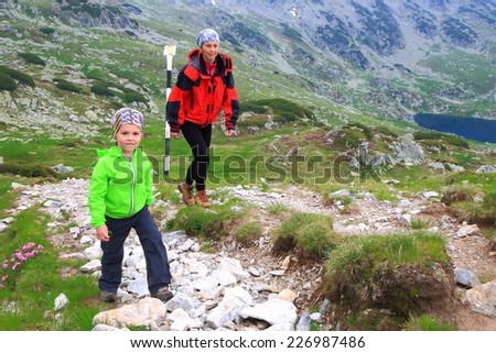 Small boy and mother climb a winding mountain trail - stock photo