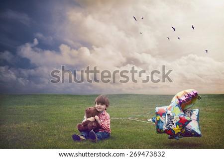 Small boy celebrating his birthday alone on empty field. - stock photo