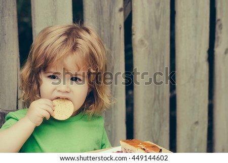 Small boy child with long blonde hair and serious face sitting at wooden table eating berry pie and biscuit outdoor near wood fence