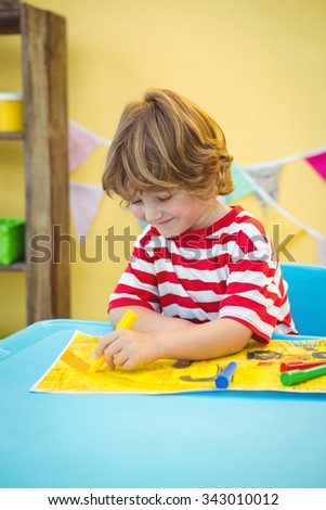 Small boy colouring in his picture at the desk - stock photo