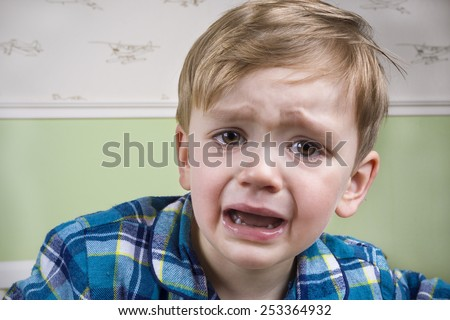 Small boy crying dramatically before bedtime - stock photo