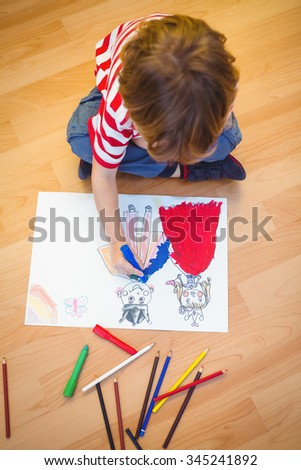 Small boy drawing on paper on the floor - stock photo