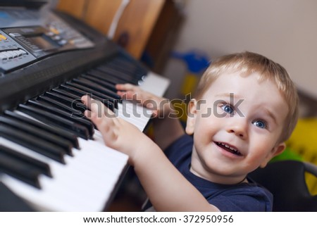 Small boy enjoys playing electric piano  (synthesizer) for the first time - stock photo