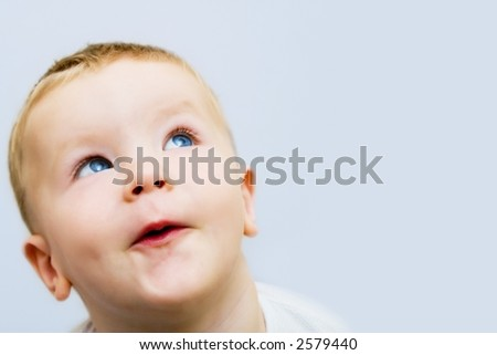Small boy excitingly looking upwards on a blue background. Soft focus. - stock photo