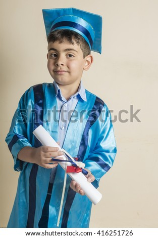 Small boy graduation from kindergarten with blue formal dress with rolled paper in his hand - stock photo